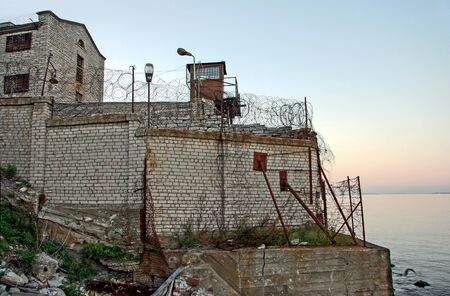Old fortified prison wall adjacent to the sea. Barbed wire on the walls. Security tower. Calm sea. 스톡 콘텐츠