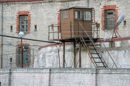 Old prison wall with barbed wire and observation tower behind it. Light brick wall, bars on the windows. Lighting lanterns.