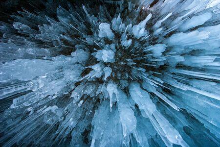 Natürlicher struktureller Hintergrund. Viele lange Eiszapfen schossen von unten. Klingt nach einer Explosion. Blaue Tönung. Winter-Hintergrund. Standard-Bild