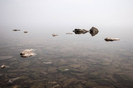 Heavy fog over a lake with clear water and stones. One can see stones with silt under water. Copy space. Banco de Imagens