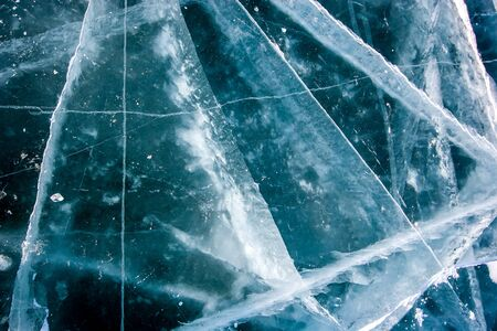 The natural texture of the transparent ice of Lake Baikal with deep cracks. Beautiful winter background.
