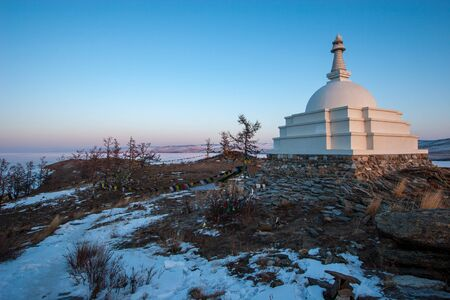 Buddhist stupa on the island of Ogoy on Lake Baikal on a background of blue sky in winter. Near the multi-colored flags on the ropes. Snow on the ground and on the lake. Soft sunset light. Stock Photo