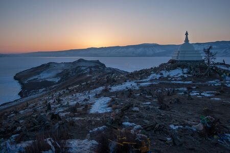 Sunset on Ogoy island on Lake Baikal overlooking a Buddhist stupa, a frozen lake and mountains behind it. The sun is just around the corner, the sky is orange.