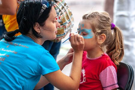 Tallinn, Estonia - August 25, 2007: Entertainment for children at the zoo. Artist paints on the face of a girl. Blue butterfly on the face of a European girl.