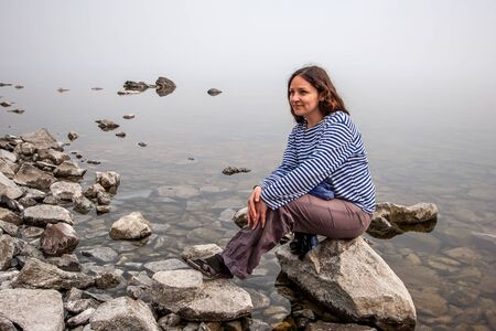 European girl tourist sitting on a large stone near the water with fog. Girl in a striped shirt and pants. The water is clear, under water overgrown with silt stones.