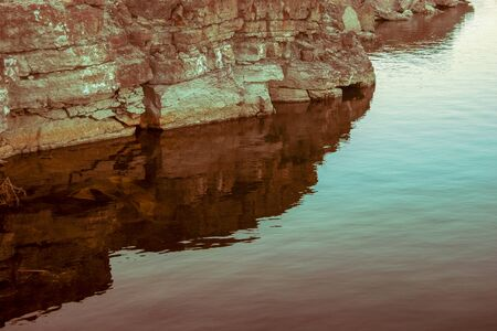 Cliff in an old quarry with reflection in the water. Limestone layers are visible. Tinted image.