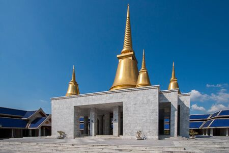 The temple building with gilded stupas on the roof against the blue sky without clouds. Four stupas are smaller along the edges and one large in the center. The building is made of gray marble.