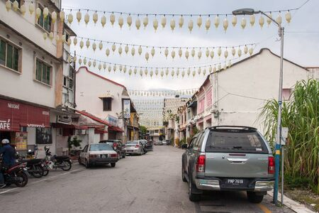 Georgetown, Malaysia - December 11, 2018: a city street decorated with garlands of lanterns in cloudy weather. Two-story houses. Cars and mopeds.