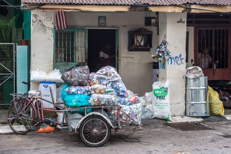 Georgetown, Malaysia - December 11, 2018: a bicycle with a trolley loaded with bags of aluminum cans. A bicycle stands next to the door with a shack. People can be seen in the doorway.