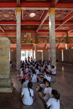Bangkok, Thailand - November 18, 2015: Monk teaches children in the temple. Children sit on the marble floor and listen to the teacher. Vertical.
