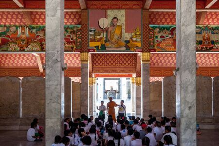 Bangkok, Thailand - November 18, 2015: Monk teacher tells something to children in the temple. Children sit on the marble floor and listen to the teacher. There are many drawings of monks on the walls 報道画像
