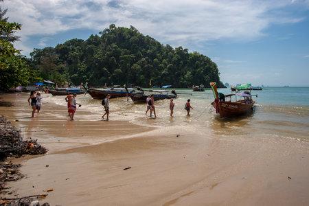 Ao Nang, Thailand - November 27, 2015: Tourists walk the chain on a long boat to sail to Railay Beach. Sunny. Many boats on the waves off the coast.