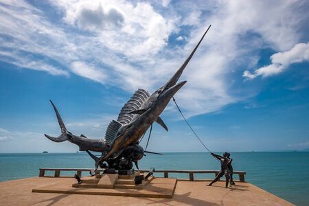 Ao Nang, Thailand - December 2015: sailfish monument on the promenade in Krabi province. Two sailors hold a large fish on a long rope. Sunny, the sky is blue with clouds.