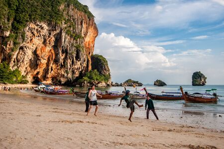 Ao Nang, Thailand - November 27, 2015: four guys play with a ball on the seashore near long boats. International team. Many moored boats. Beautiful cliffs on the shore. Blue sky with clouds. 報道画像