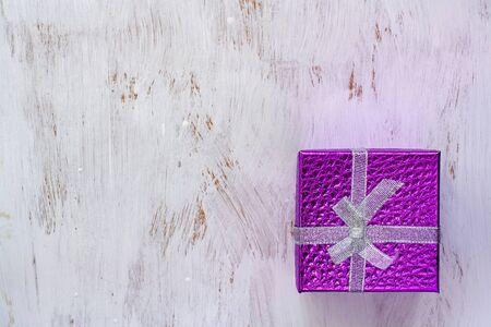 Flat lay. Gift purple box with a bow on a white surface painted with a brush. Copy space for text.