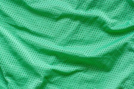 Fabric texture. Green fabric with holes and creases.