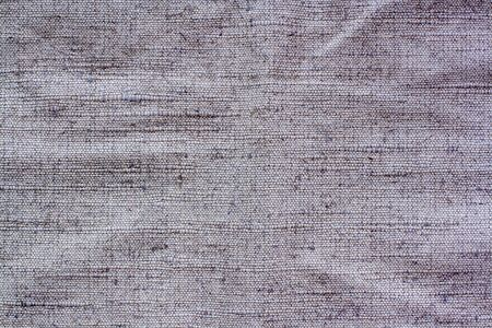 Gray fabric texture with textured stitches. Bulges and bumps in textiles.