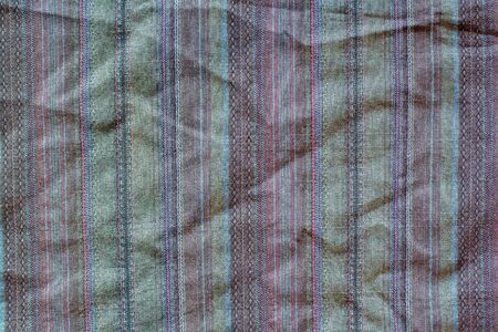 Fabric texture with multi-colored vertical stripes. A lot of stitches on the fabric. Red, green, brown colors.