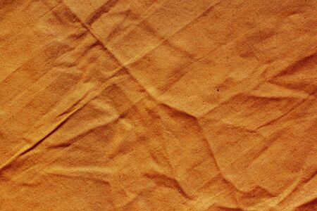 Texture of rough dense fabric of orange color. The fabric is wrinkled.