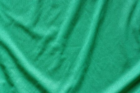 Green fabric texture. The fabric is wavy. The surface is uneven.
