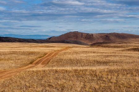 A road in the steppe going to the hills. Yellow grass. The weather is cloudy. Mountains in the distance. Stock Photo