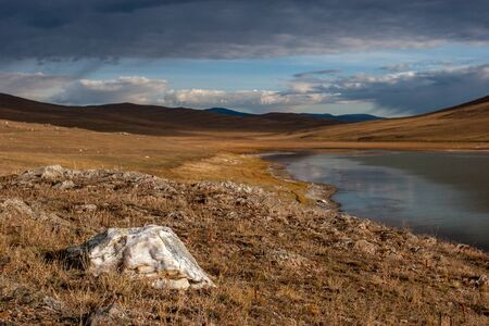 Big stone in the steppe by the lake. Hills beyond the lake. Clouds in the sky. The lake is green dark.