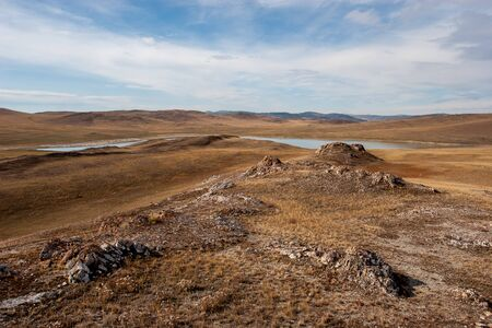 Steppe with hills and a lake. Brown grass on the ground. There are clouds in the sky. Reklamní fotografie