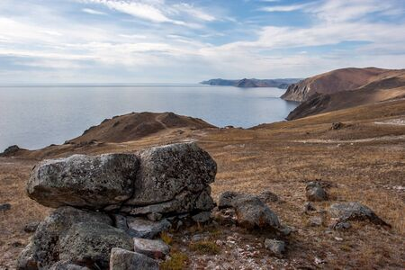 Large stones on the shore of Lake Baikal. High rocky shore. There are clouds on the blue sky. The lake is calm. Reklamní fotografie