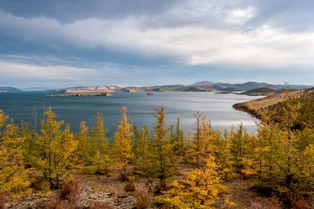 Autumn landscape with trees and a view of Lake Baikal. Yellow trees in the foreground. Clouds in the sky. Horizontal. Reklamní fotografie
