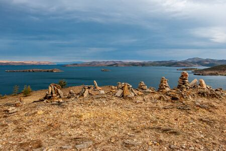 Stones piled by pyramids and a view of Lake Baikal. Hills beyond the lake. Several islands in the lake. Cloudy and gloomy. Horizontal. Reklamní fotografie