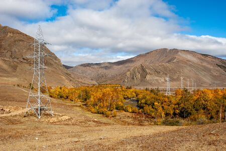 A river flows between mountains with yellow trees along the shore and power lines. Autumn colors. Clouds in the sky. Horizontal.