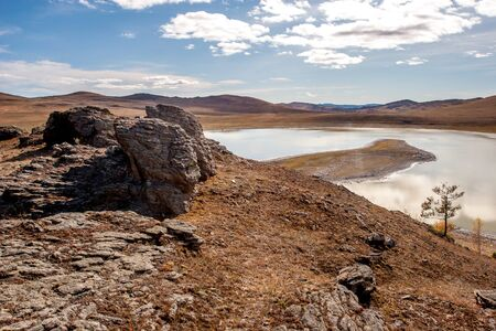 View of the lake in the steppe with stones in the foreground. Sunny. The sky with clouds. Hills beyond the lake. Horizontal.