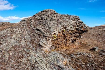 An interesting stone in the steppe with layers with an interesting structure. Dilapidated stones. Blue sky. Horizontal.