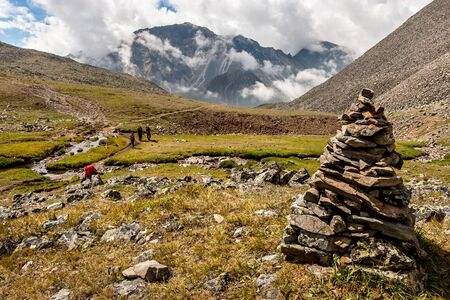 A large cairn in the foreground of a mountain landscape. Low white clouds over the mountains. Tourists with backpacks go along the path along the slope. A lot of stones on the ground. Horizontal.