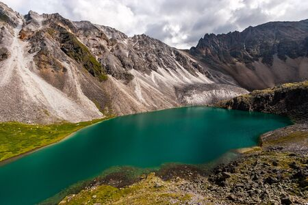 Amazing colorful lake with turquoise water next to the cliffs in the mountains. There are a lot of stones around. The sky is overcast. Horizontal.