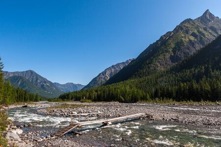 A river in the mountains with a bridge. A lot of stones in the riverbed. High mountains around and a lot of coniferous forest. Blue sky without clouds. Horizontal.