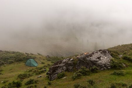 A lonely green tent stands in the fog in the mountains. A large boulder in the foreground. Green vegetation around. Copy space. Horizontal.