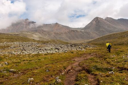 Tourists with large backpacks go on a hiking trail in the mountains. Clouds above the tops of high mountains. Stone talus. Green grass on the slope. Horizontal.