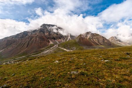 Large high mountain in the clouds with stone scree. Blue sky with clouds. Grass with stones on the slope. Horizontal.