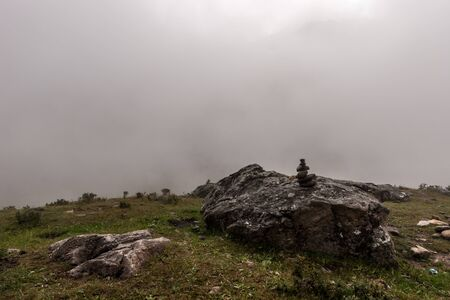 A small pyramid stands on a large boulder in the mountains with dense fog in the background. Gloomy weather. Horizontal.