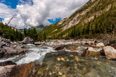 A mountain river with a wide channel flows over the stones. The river has a rocky bottom. Green forest on the hillsides and low white clouds on a blue sky. Horizontal. Reklamní fotografie