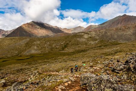 Tourists with backpacks and sticks are walking in the mountains. Beautiful mountains in the background with blue sky and clouds. There are a lot of stones and boulders on the earth. Horizontal. Reklamní fotografie