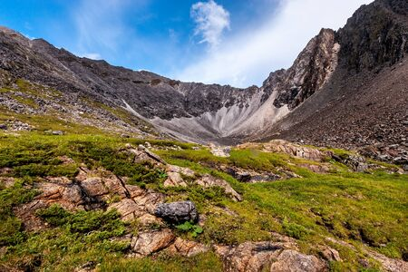 High rocky ridge and large stones in the foreground. Green grass on the ground. Blue sky with clouds. Horizontal. Reklamní fotografie