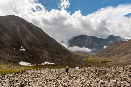 Hiker man with a backpack is walking among the high mountains on stones on the ground. High mountains and low white clouds. Valley between the mountains. Horizontal.