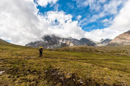 Hiker is walking in the mountains with a backpack and a stick. High mountains in the distance with hidden peaks in the clouds. Rocky ground. Shadows from the clouds on the mountains. Horizontal. Reklamní fotografie