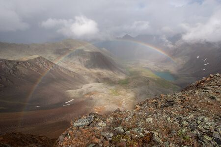 A full rainbow in a valley photographed from above from a mountain pass. Gloomy clouds in the sky. Below you can see the lake. Horizontal.