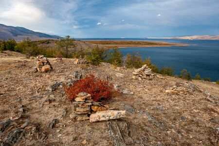 Autumn landscape with a view of Lake Baikal and piles of stones in the foreground. Red bush in the foreground. Cloudy Horizontal.