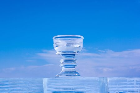 Large ice bowl on a background of blue sky. The cup stands on an ice pedestal. Cracks and scratches on the ice. There are clouds in the sky. Horizontal. Banco de Imagens