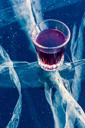 Alcohol in a glass and clean ice with beautiful deep cracks. A glass with red tincture stands on the transparent ice of the lake. Vertical.