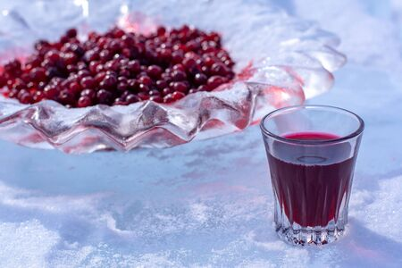 Alcoholic red tincture and red cranberries in an ice dish. Liquor in a glass stands in the snow. Focus on the glass. Horizontal.
